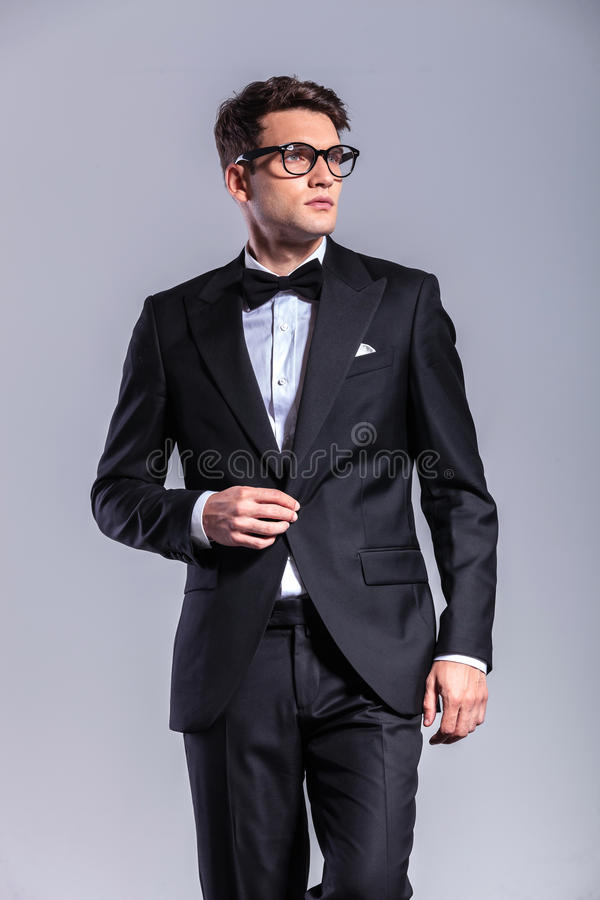 Young handsome business man opening his jacket. While looking away from the camera royalty free stock images