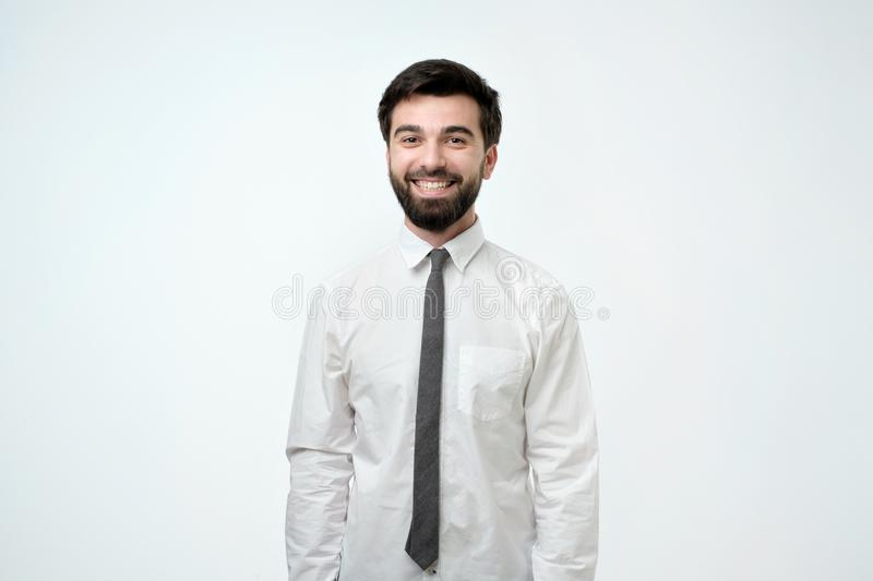 Young handsome business man over background happy face smiling and looking at the camera. royalty free stock photos