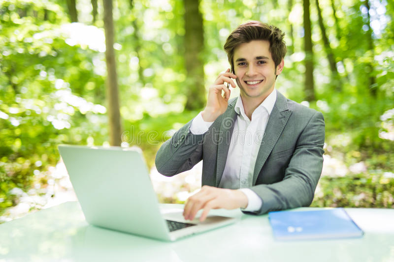 Portrait of young handsome business man sitting at office desk in the green park or forest and work at laptop while talk at phone. Young handsome business man royalty free stock image