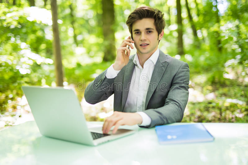 Portrait of young handsome business man sitting at office desk in the green park or forest and work at laptop while talk at phone. Young handsome business man stock images