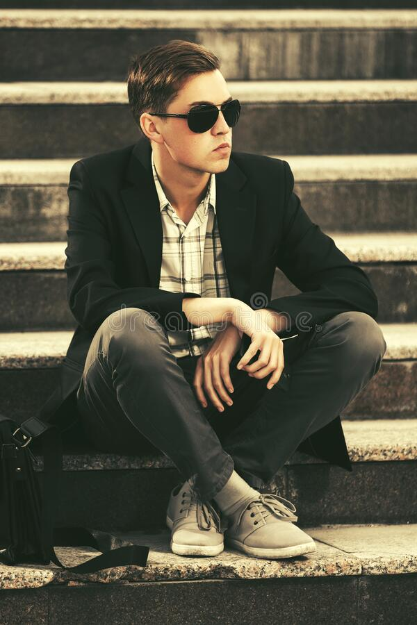 Young handsome business man in sunglasses sitting on steps. Stylish male model wearing black blazer and gray pants royalty free stock photography