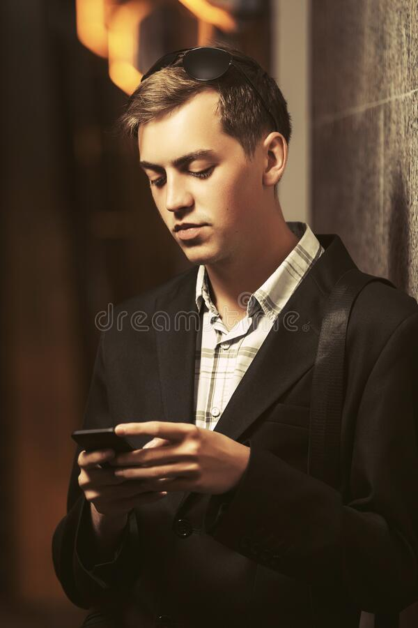 Young handsome business man using cell phone on city street. Stylish fashion male model in black blazer stock photography