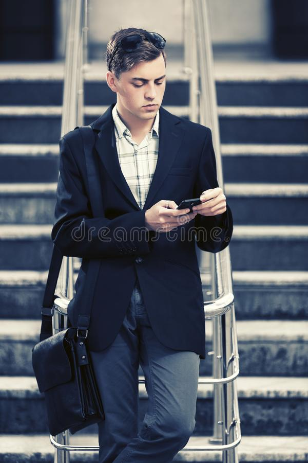 Young handsome business man using smart phone in city street royalty free stock images