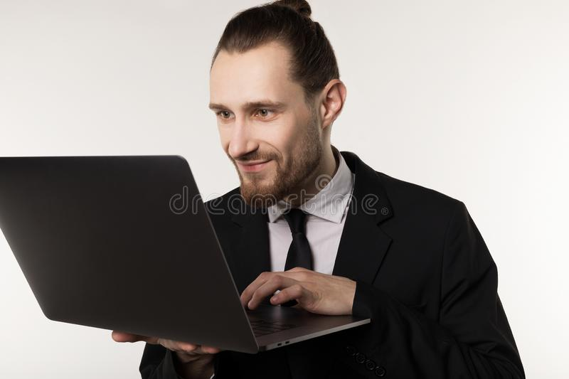 Young handsome businessman with beard and trendy hairstyle wearing black suit and tie royalty free stock photos