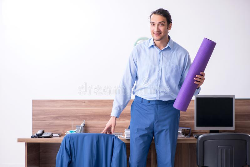 Young handsome businessman doing exercises at workplace. The young handsome businessman doing exercises at workplace stock photography