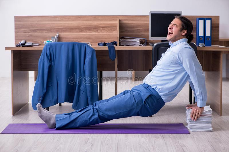 Young handsome businessman doing exercises at workplace. The young handsome businessman doing exercises at workplace stock image