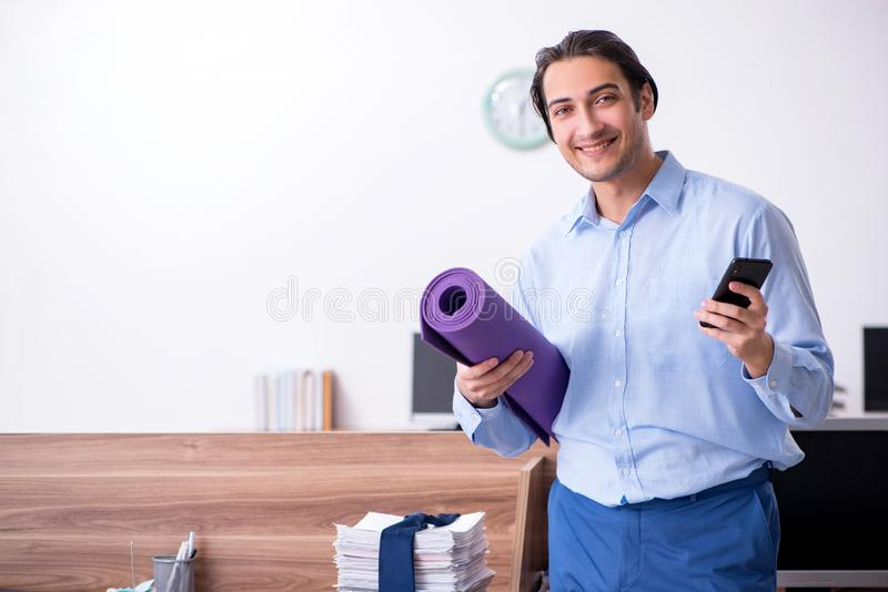 Young handsome businessman doing exercises at workplace. The young handsome businessman doing exercises at workplace royalty free stock photography