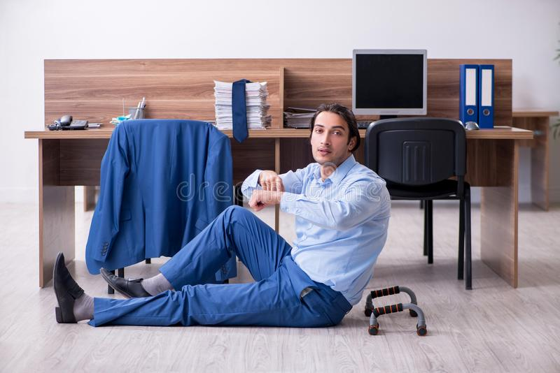 Young handsome businessman doing exercises at workplace. The young handsome businessman doing exercises at workplace stock photos