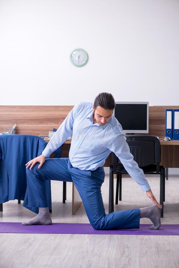 Young handsome businessman doing exercises at workplace. The young handsome businessman doing exercises at workplace royalty free stock image