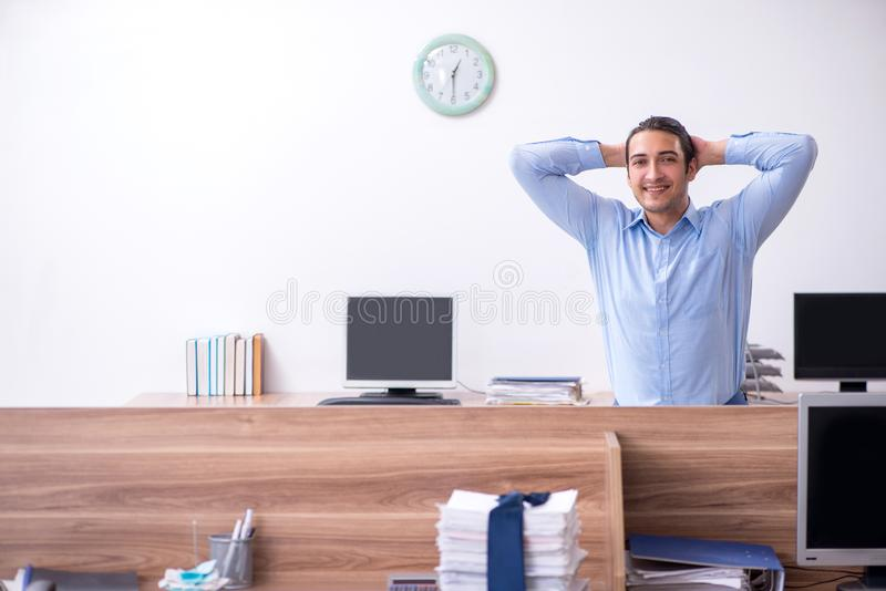 Young handsome businessman doing exercises at workplace. The young handsome businessman doing exercises at workplace royalty free stock photos