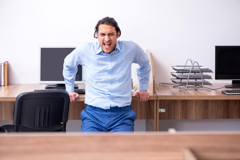 Young handsome businessman doing exercises at workplace. The young handsome businessman doing exercises at workplace royalty free stock photo