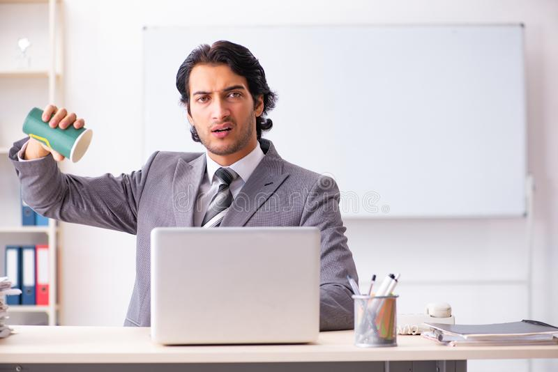 The young handsome businessman employee sitting in the office. Young handsome businessman employee sitting in the office stock image