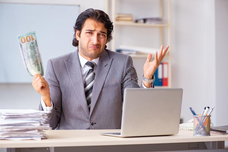 The young handsome businessman employee sitting in the office. Young handsome businessman employee sitting in the office royalty free stock photo