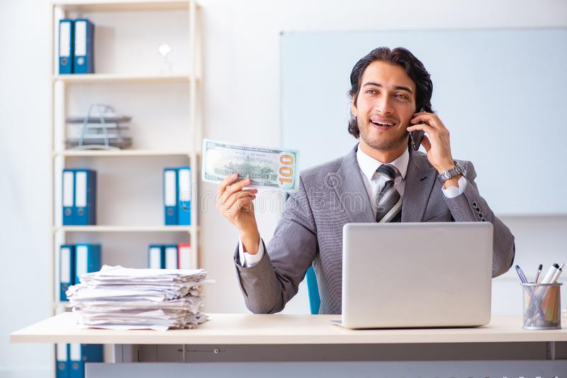 The young handsome businessman employee sitting in the office. Young handsome businessman employee sitting in the office royalty free stock photography