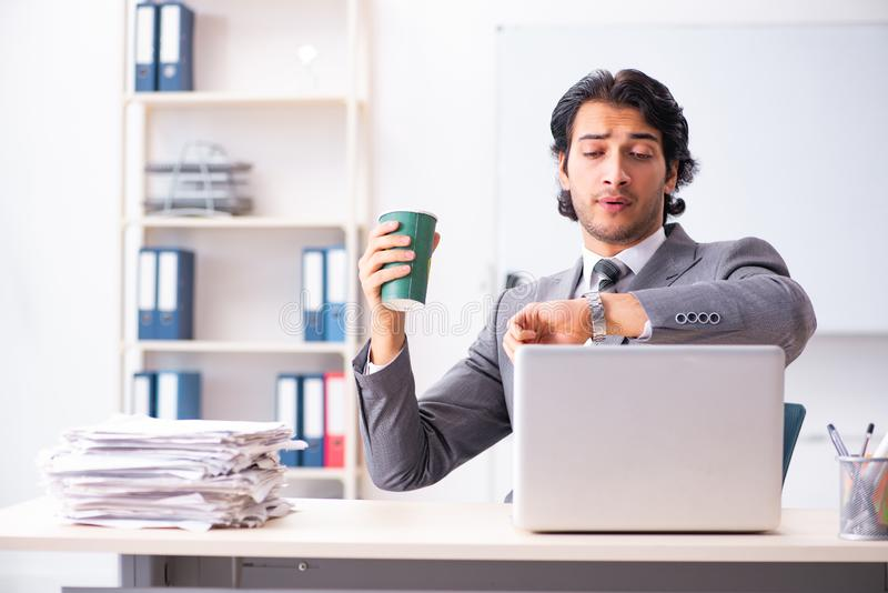 The young handsome businessman employee sitting in the office. Young handsome businessman employee sitting in the office stock images