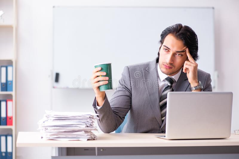 The young handsome businessman employee sitting in the office. Young handsome businessman employee sitting in the office stock photo