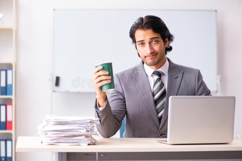 The young handsome businessman employee sitting in the office. Young handsome businessman employee sitting in the office royalty free stock image