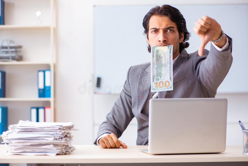 The young handsome businessman employee sitting in the office. Young handsome businessman employee sitting in the office stock photography