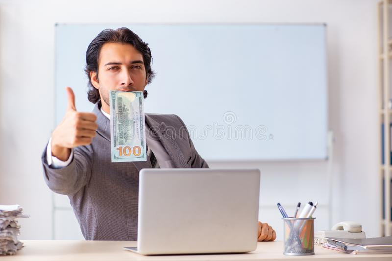 The young handsome businessman employee sitting in the office. Young handsome businessman employee sitting in the office royalty free stock photos