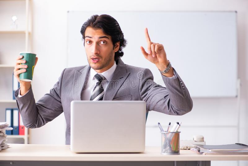 The young handsome businessman employee sitting in the office. Young handsome businessman employee sitting in the office royalty free stock images