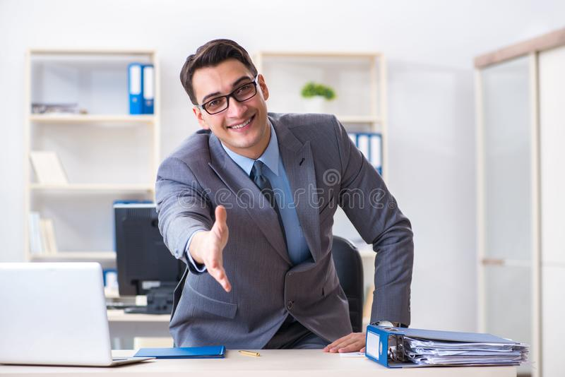 The young handsome businessman employee working in office at desk royalty free stock photo