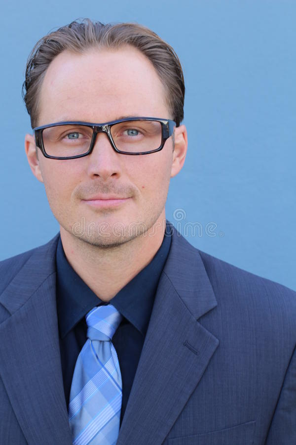 Young handsome businessman with glasses against blue background stock photography