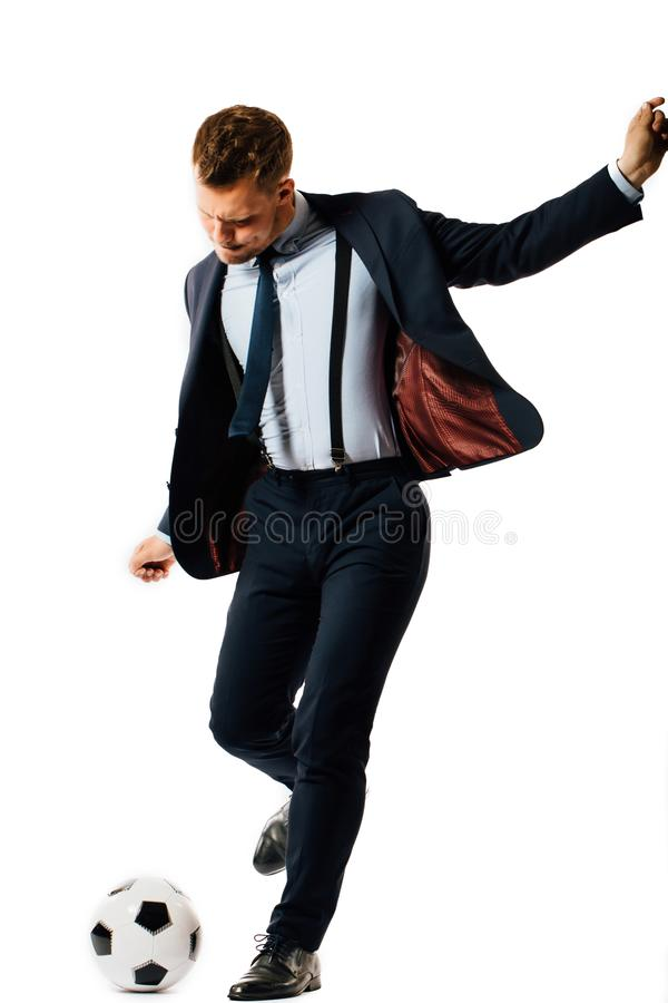 Young handsome businessman manager kicking a soccer ball on white background isolated. stock image