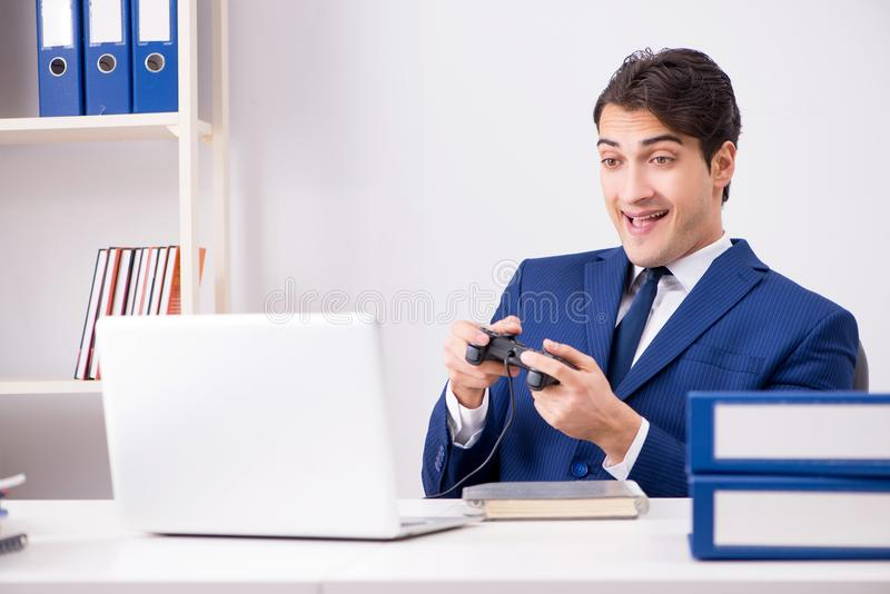 The young handsome businessman playing computer games at work office. Young handsome businessman playing computer games at work office royalty free stock image