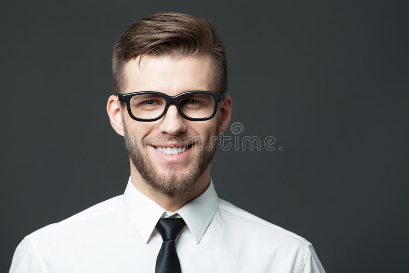 Young handsome businessman portrait on dark gray background. royalty free stock image