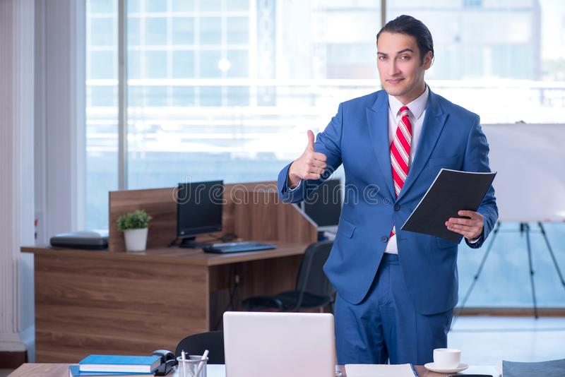 Young handsome businessman sitting in the office royalty free stock photo