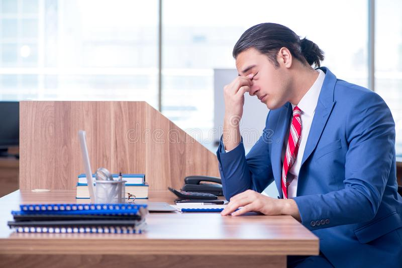 Young handsome businessman sitting in the office royalty free stock image