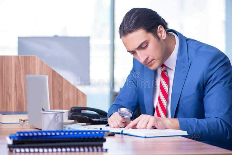 Young handsome businessman sitting in the office royalty free stock photography