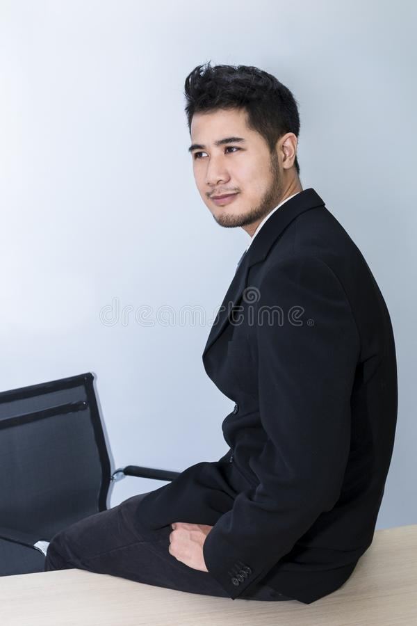 Young handsome businessman smiling and smart sit on table at office stock images