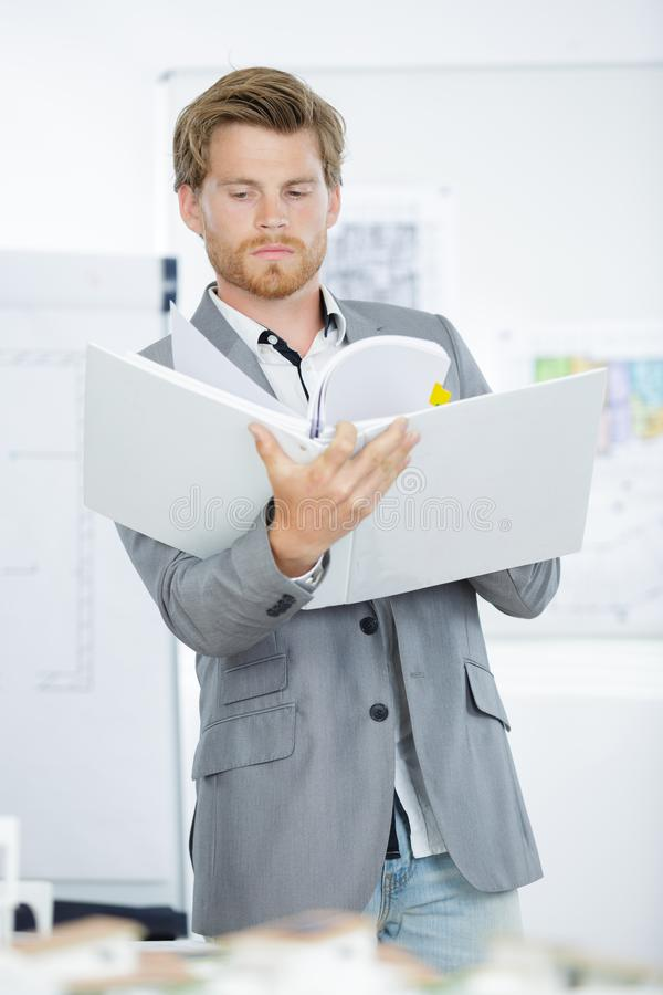 Young handsome businessman in suit holding folders. Young stock photos