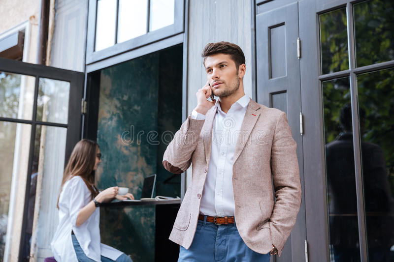 Young handsome businessman talking on mobile phone outdoors at cafe royalty free stock photo