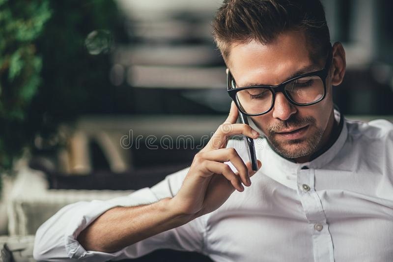 Young handsome businessman is talking on phone, sitting at table in cafe. Man in glasses makes call. Business person in. Shirt has good stock photo