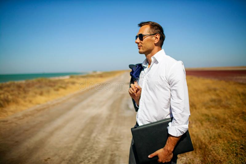 Young handsome businessman wearing in a white shirt walking with laptop on the beach. stock image