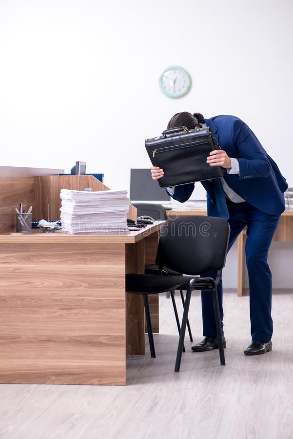 Young handsome businessman working in the office. The young handsome businessman working in the office stock image