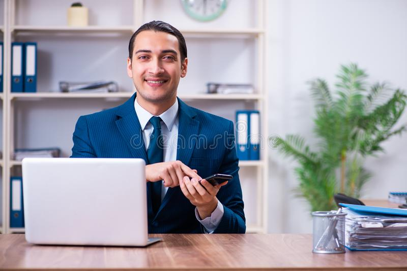 Young handsome businessman working in the office stock photography