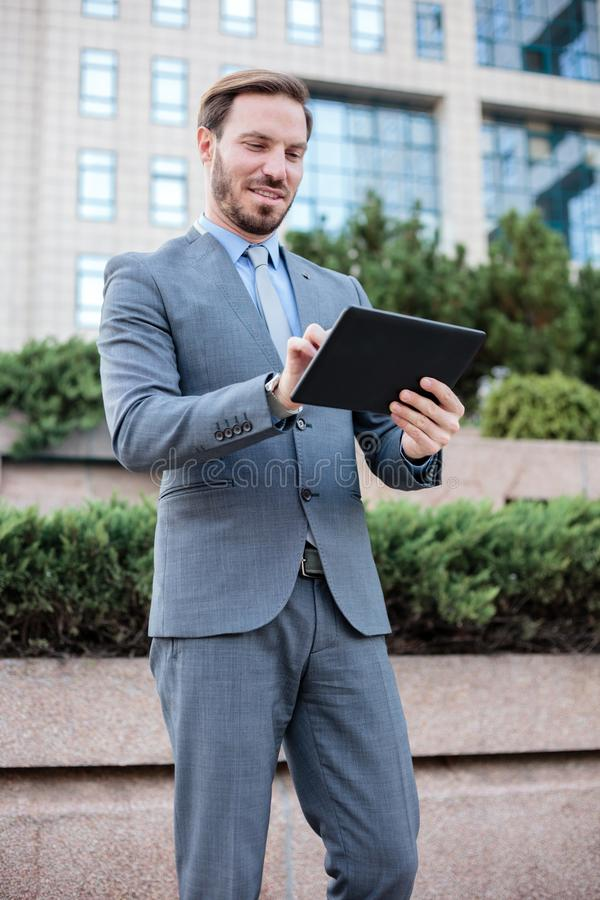 Young, handsome businessman working on a tablet in front of an office building. Low angle view. Work and stay connected anywhere concept stock photos