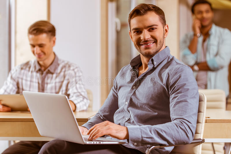 Young handsome businessmen coworking. Young handsome dark-haired businessman in casual clothes smiling and using laptop, in the background two other businessmen royalty free stock photo