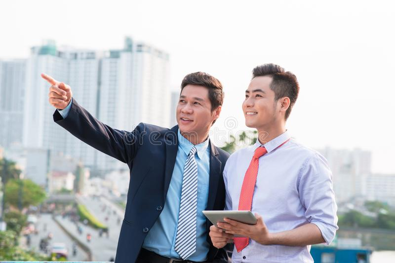 Young handsome businessmen discussing project on digital tablet computer outdoors.  stock photography