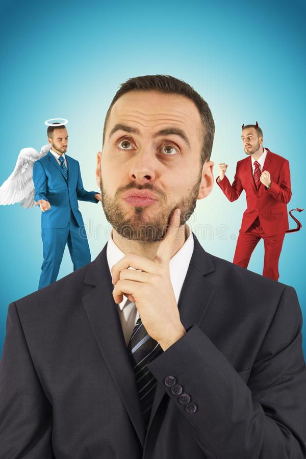 Businessman with angel and devil on his shoulders. stock photos