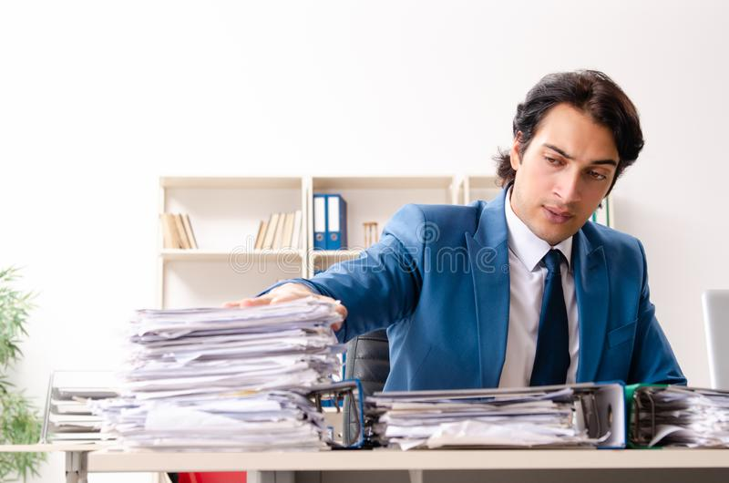 The young handsome busy employee sitting in office. Young handsome busy employee sitting in office royalty free stock photography