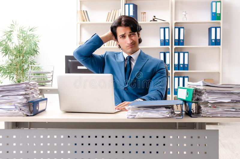 The young handsome busy employee sitting in office. Young handsome busy employee sitting in office stock image