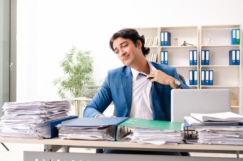 Young handsome busy employee sitting in office. The young handsome busy employee sitting in office stock photo