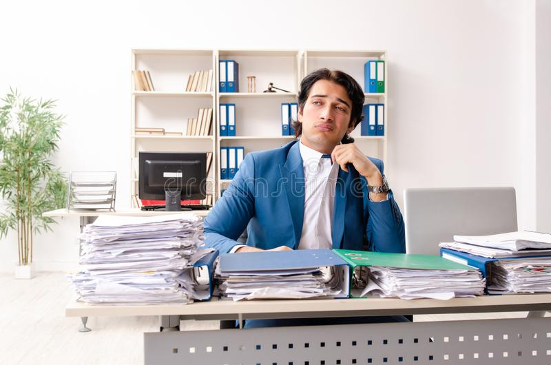 Young handsome busy employee sitting in office. The young handsome busy employee sitting in office royalty free stock image