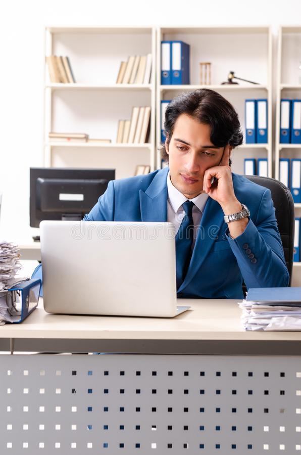 The young handsome busy employee sitting in office. Young handsome busy employee sitting in office stock images