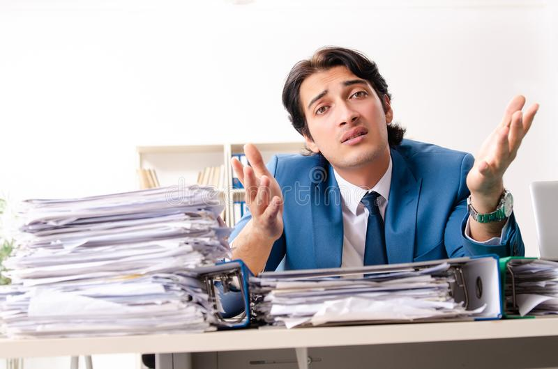 The young handsome busy employee sitting in office. Young handsome busy employee sitting in office stock photo