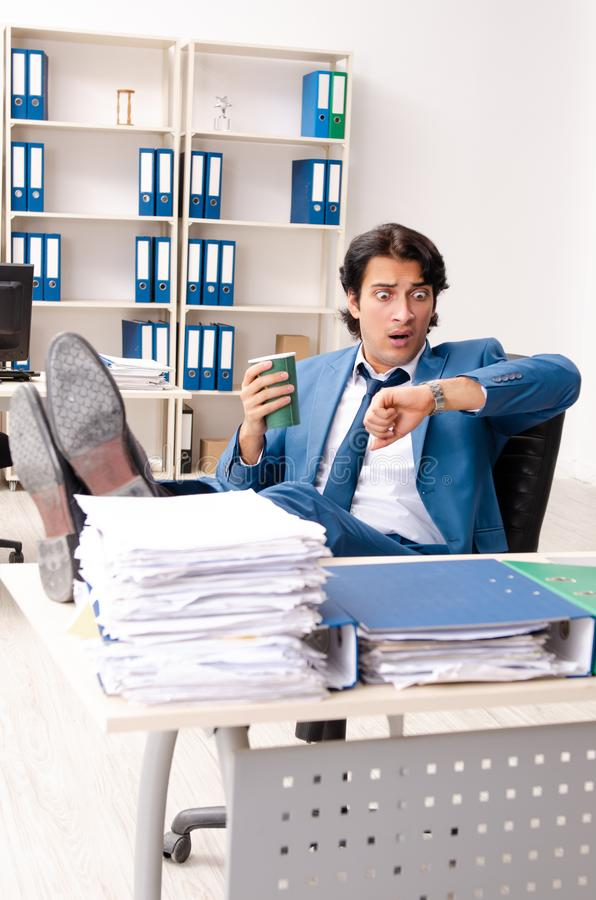 The young handsome busy employee sitting in office. Young handsome busy employee sitting in office stock photos